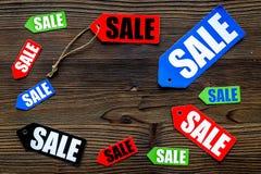 Farbige Verkaufsaufkleber auf dunklem hölzernem copyspace Draufsicht des Hintergrundes Lizenzfreie Stockfotos