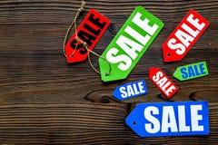 Farbige Verkaufsaufkleber auf dunklem hölzernem copyspace Draufsicht des Hintergrundes Stockfotografie