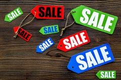 Farbige Verkaufsaufkleber auf dunklem hölzernem copyspace Draufsicht des Hintergrundes Lizenzfreie Stockbilder