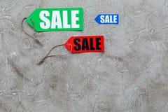 Farbige Verkaufsaufkleber auf hellem Steincopyspace Draufsicht des hintergrundes Lizenzfreie Stockbilder