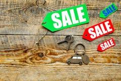 Farbige Verkaufsaufkleber und Autoschlüssel auf hölzernem copyspace Draufsicht des Hintergrundes Stockfoto