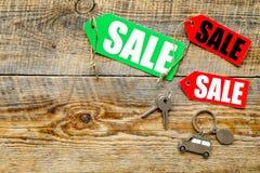 Farbige Verkaufsaufkleber und Autoschlüssel auf hölzernem copyspace Draufsicht des Hintergrundes Stockfotografie