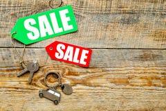 Farbige Verkaufsaufkleber und Autoschlüssel auf hölzernem copyspace Draufsicht des Hintergrundes Lizenzfreie Stockbilder