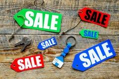 Farbige Verkaufsaufkleber und Hausschlüssel auf Draufsicht des hölzernen Hintergrundes Lizenzfreie Stockbilder