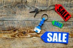 Farbige Verkaufsaufkleber und Hausschlüssel auf hölzernem copyspace Draufsicht des Hintergrundes Lizenzfreie Stockbilder