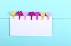 Farbige Wäscheklammerherzen und leere Karte Lizenzfreies Stockbild