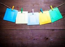 Farbige Wäscheklammern mit foto Rahmen auf Seil auf einem Holztisch O Stockbild