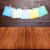 Farbige Wäscheklammern mit Fotorahmen auf Seil auf einer hölzernen Wand O Stockfoto