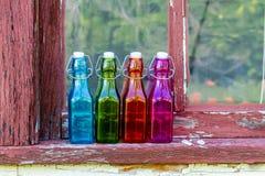 Farbige Weinlese-Flaschen auf Fensterbrett Stockfotografie