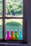 Farbige Weinlese-Flaschen auf Fensterbrett Lizenzfreie Stockfotos