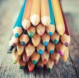 Farbige zeichnende Bleistifte auf altem Schreibtisch Stilisiertes Bild der Weinlese Lizenzfreies Stockfoto