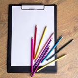 Farbige zeichnende Bleistifte und Klemmbrett mit leerem Papier auf hölzernem Lizenzfreies Stockbild