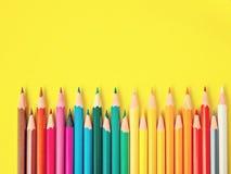Farbiger Bleistift auf gelbem Papierhintergrund für Zeichnungsfarbkreis Stockfotos