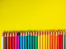 Farbiger Bleistift auf gelbem Papierhintergrund für Zeichnungsfarbkreis Stockfotografie