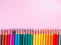 Farbiger Bleistift auf rosa Papierhintergrund für Zeichnungsfarbkreis Stockfotografie