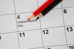 Farbiger Bleistift mit Viertel von Juli-Kalender Stockbilder