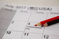Farbiger Bleistift mit Viertel von Juli-Kalender Stockbild