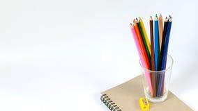 Farbiger Bleistift und Bleistiftspitzer im Glas auf einem Buch Lizenzfreie Stockfotos