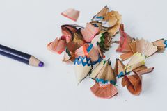 Farbiger Bleistift und Sägemehl verursachten durch einen Bleistiftspitzer auf dem weißen Blackground lizenzfreie stockfotografie