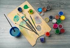 Farbiger Bleistiftpinsel gegen dunkle Tabelle Lizenzfreie Stockbilder