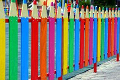 Farbiger dekorativer Zaun in Form von Bleistiften auf der Straße nahe dem Spielplatz Stockbilder