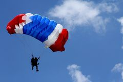 Farbiger Fallschirm auf blauem Himmel Lizenzfreies Stockbild