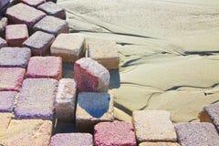 Farbiger konkreter Bodenbelag baute auf einem Substrat des Sandes zusammen; Art Lizenzfreie Stockbilder
