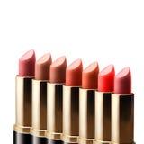 Farbiger Lippenstift, der in Folge auf weißem Hintergrund steht stockfotos