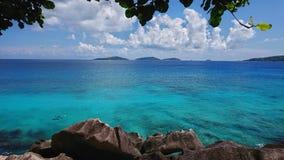 Farbiger Ozean durch die Bucht Standort La Digue Seychellen lizenzfreie stockfotografie