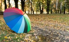 farbiger Regenschirm auf Herbstlaub Lizenzfreie Stockfotografie