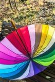 Farbiger Regenschirm im Freien, der auf einer Bank liegt stockbilder
