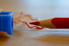 Farbiger roter Bleistift, Bleistiftspitzer und Schnitzel auf Holztisch Lizenzfreie Stockbilder
