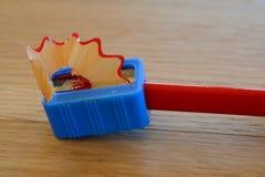 Farbiger roter Bleistift, Bleistiftspitzer und Schnitzel auf Holztisch Stockfoto