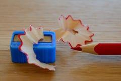 Farbiger roter Bleistift, Bleistiftspitzer und Schnitzel auf Holztisch Stockfotos