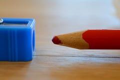 Farbiger roter Bleistift und Bleistiftspitzer auf Holztisch Stockbilder