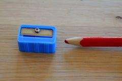 Farbiger roter Bleistift und Bleistiftspitzer auf Holztisch Lizenzfreies Stockfoto