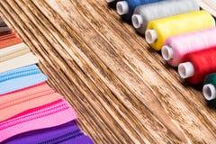 Farbiger Thread ausgebreitet vor Blitz auf einem Holztisch Stockfotografie