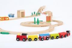 Farbiger Zug mit Autos und hölzerner Spielzeugeisenbahn Lizenzfreies Stockfoto