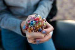 Farbiges antistress Spielzeug in der Hand einer schönen jungen Frau Lizenzfreies Stockfoto