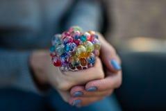 Farbiges antistress Spielzeug in der Hand einer schönen jungen Frau Lizenzfreie Stockfotos