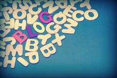 Farbiges Blog-Zeichen auf grünem Hintergrund mit verschiedenen Buchstaben Stockbilder