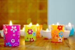 Farbiges Glas mit brennenden Kerzen Stockbilder