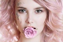 Farbiges Haar Schönheitsfrauenporträt der jungen gelockten Frau mit dem rosa Haar, perfektes Kunstmake-up mit Funkeln Rose in ihr Lizenzfreie Stockfotos