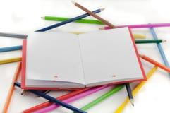 Farbiges Notizbuch und Bleistifte auf weißem Hintergrund Stockbild