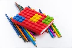 Farbiges Notizbuch und Bleistifte auf weißem Hintergrund Stockfotos