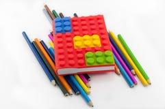 Farbiges Notizbuch und Bleistifte auf weißem Hintergrund Lizenzfreie Stockfotografie
