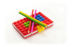 Farbiges Notizbuch und Bleistifte auf weißem Hintergrund Stockfotografie