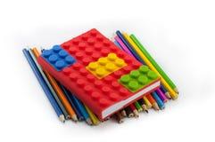 Farbiges Notizbuch und Bleistifte auf weißem Hintergrund Lizenzfreies Stockbild