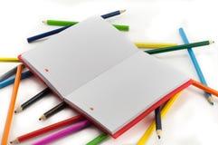Farbiges Notizbuch und Bleistifte auf weißem Hintergrund Stockbilder