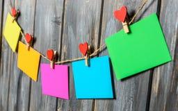 Farbiges Papier bedeckt auf Thread mit Herz geformtem hölzernem Hintergrund der Wäscheklammer Lizenzfreie Stockbilder
